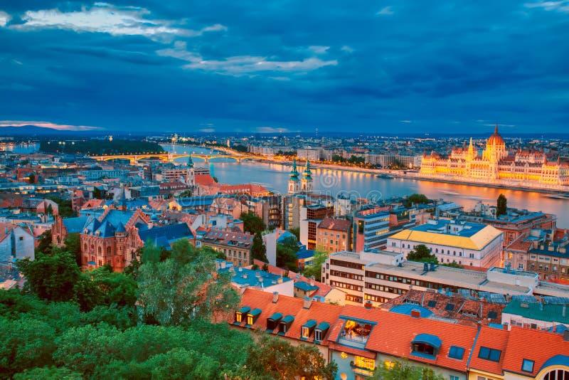 Ansicht von belichtetem Parlament und Flussufer von der Donau in Budapest, Ungarn während des Sonnenuntergangs mit drastischem Hi lizenzfreies stockbild