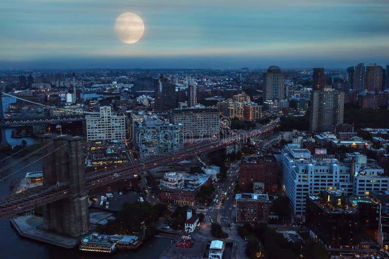 Ansicht von den Höhen der Nachtstadt Ein enormer Vollmond über der Stadt am Abend Stadt New York stockbild