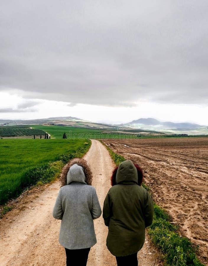 Ansicht von den Paaren, die auf einen Schotterweg im schönen Parkland gehen lizenzfreie stockfotografie