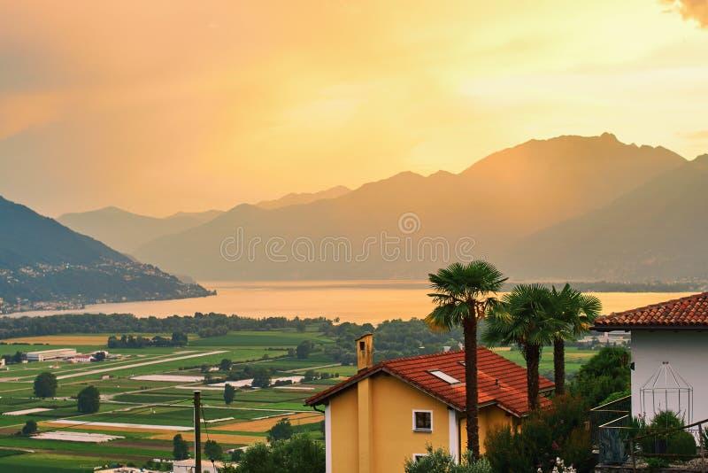 Ansicht von der ländlichen Süd-Schweiz mit Häusern, Bauernhöfen, Weinbergen, Alpenbergen und See Maggiore lizenzfreie stockfotos