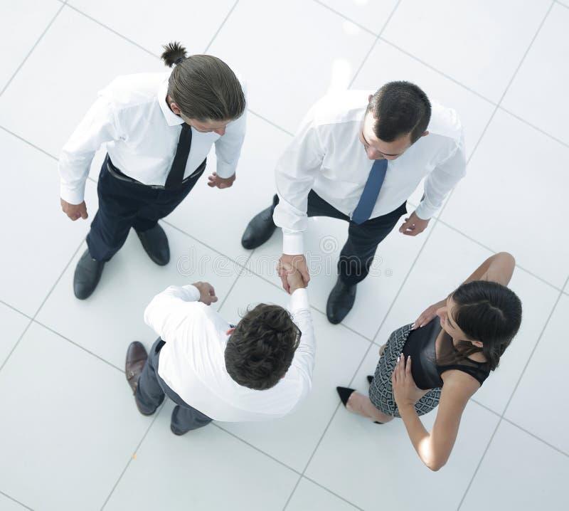 Ansicht von der Oberseite willkommene Kollegen, die Hände im Büro rütteln stockfotografie