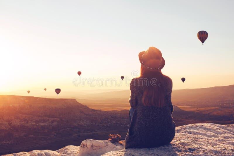 Ansicht von der Rückseite eines Mädchens in einem Hut sitzt auf einem Hügel und betrachtet Luftballone lizenzfreies stockfoto