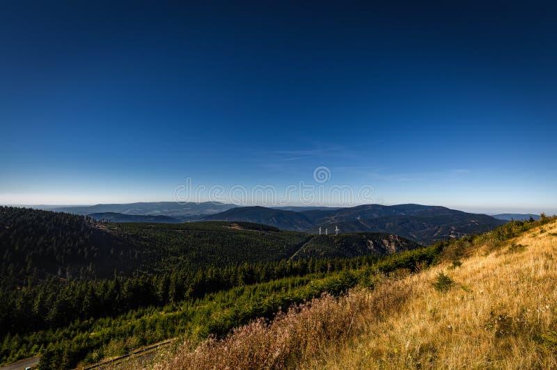 Ansicht von Dlouhe-strane Spitzenreservoir zum Tal mit Windkraftanlage und grünem Wald, dunkelblauer Himmel lizenzfreies stockfoto
