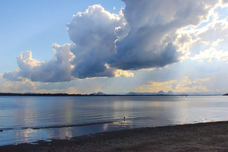 Ansicht von drastischen Wolken und der frühe Sonnenuntergang, der von Bribie-Insel über dem Bimsstein schaut, lassen zu den Glasb stockfotografie
