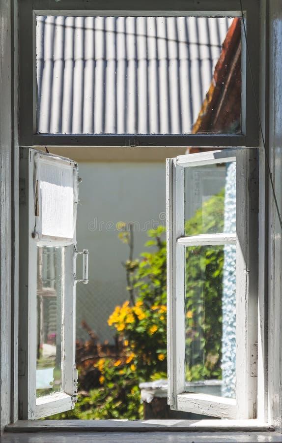 Ansicht von einem alten ländlichen Fenster in einem sonnigen Sommerhof lizenzfreies stockfoto
