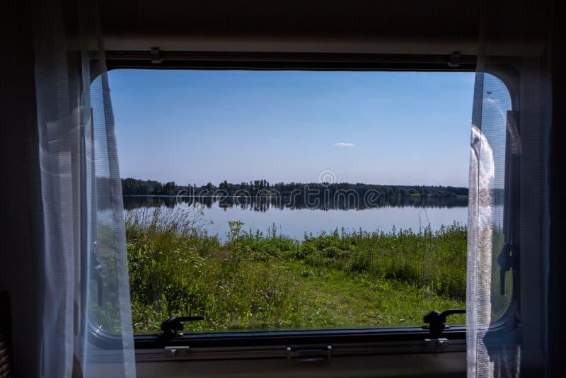 Ansicht von einem Fenster des Campers zur schönen Seelandschaft lizenzfreies stockfoto