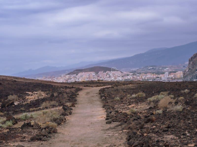 Ansicht von einem Wanderweg eines unfruchtbaren Vulkanbereichs zur entfernten Stadt von Los Cristianos lizenzfreies stockfoto