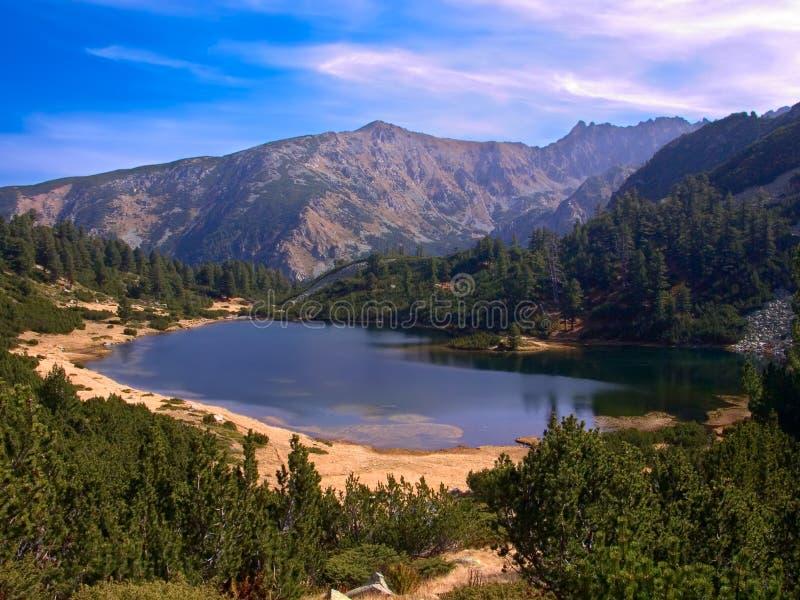 Ansicht von Glazial- See mit einigen Bergen im Hintergrund im Nationalpark Pirin stockfotos