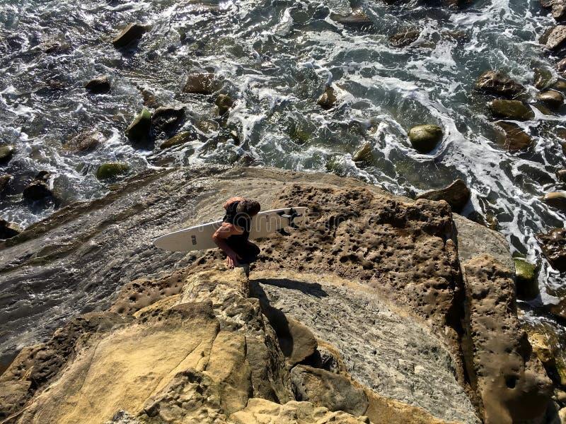 Ansicht von oben genanntem des Surfers, der entlang schroffe Küstenlinie geht lizenzfreies stockbild