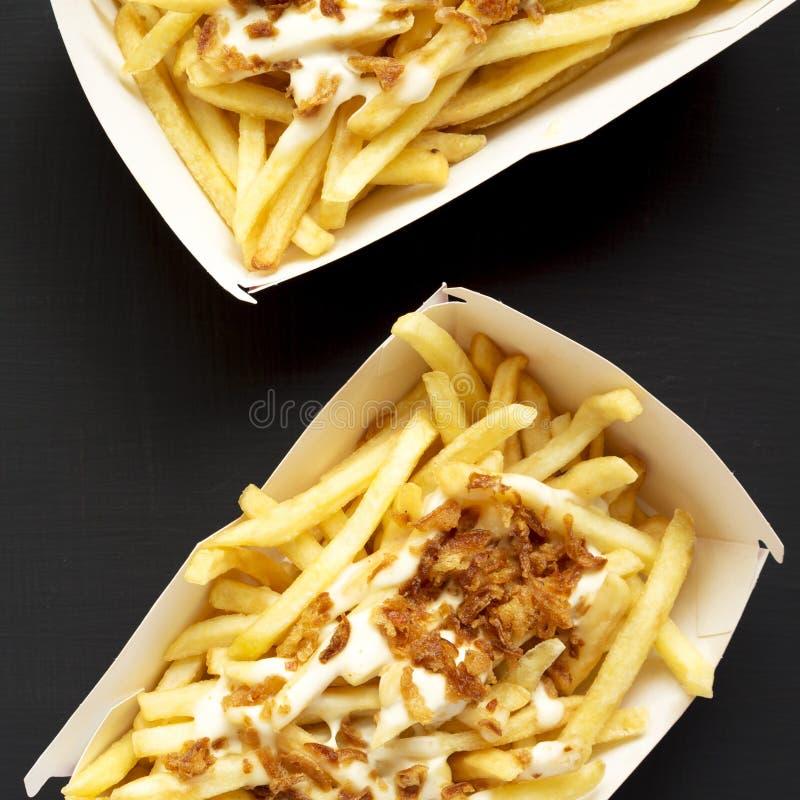 Ansicht von oben genanntem, Pommes-Frites mit Käsesoße und gebratene Zwiebel in den Papierkästen auf einem schwarzen Hintergrund  lizenzfreies stockbild