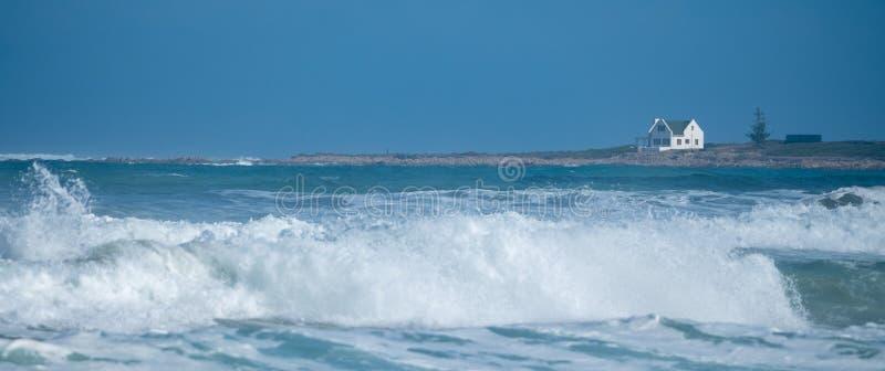 Ansicht von Ozean und von wei?em Haus bei Kanon auf der Austern-F?nger-Spur nahe Boggams-Bucht auf dem Garten-Weg, S?dafrika stockbilder
