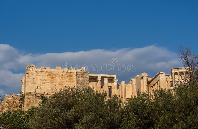 Ansicht von Propylaea-Eingang zum Akropolisbereich auf Athen, Griechenland gegen klaren blauen Himmel und Grün stockbild