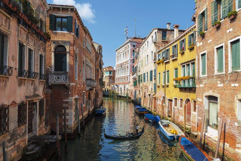 Ansicht von Stadtbild mit bunten Gebäuden auf den Banken des Kanals und der Gondel mit Touristen, Venedig lizenzfreie stockfotografie