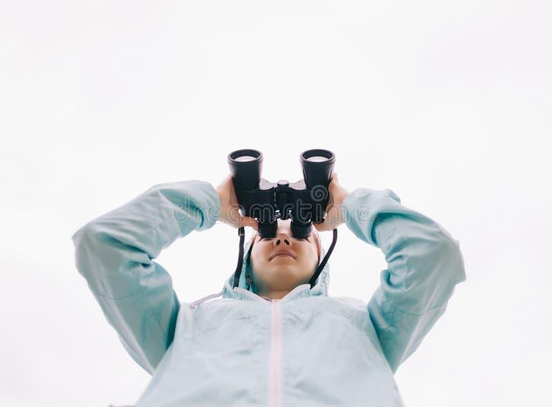 Ansicht von unten der Reisendfrau aufpassend mit Ferngläsern lizenzfreies stockbild