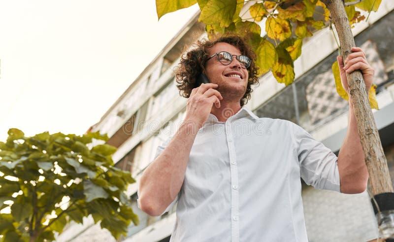 Ansicht von unten des glücklichen hübschen Geschäftsmannes, der auf der Straße bei draußen stehen und der Anwendung von Smartphon lizenzfreie stockfotografie