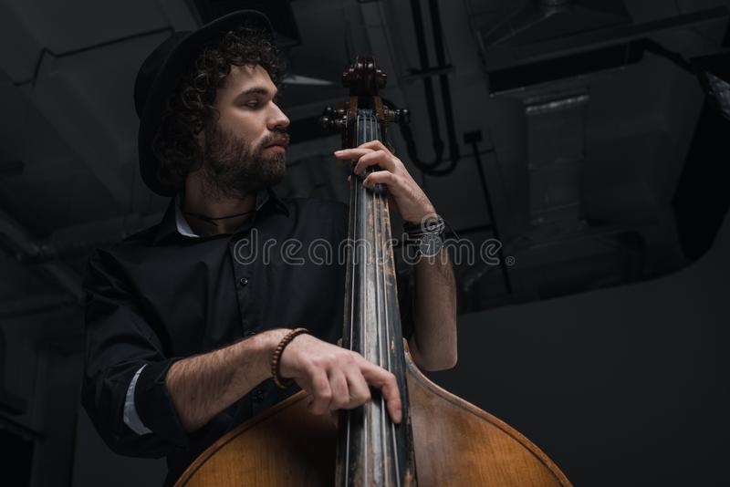 Ansicht von unten des jungen hübschen Musikers stockfotografie