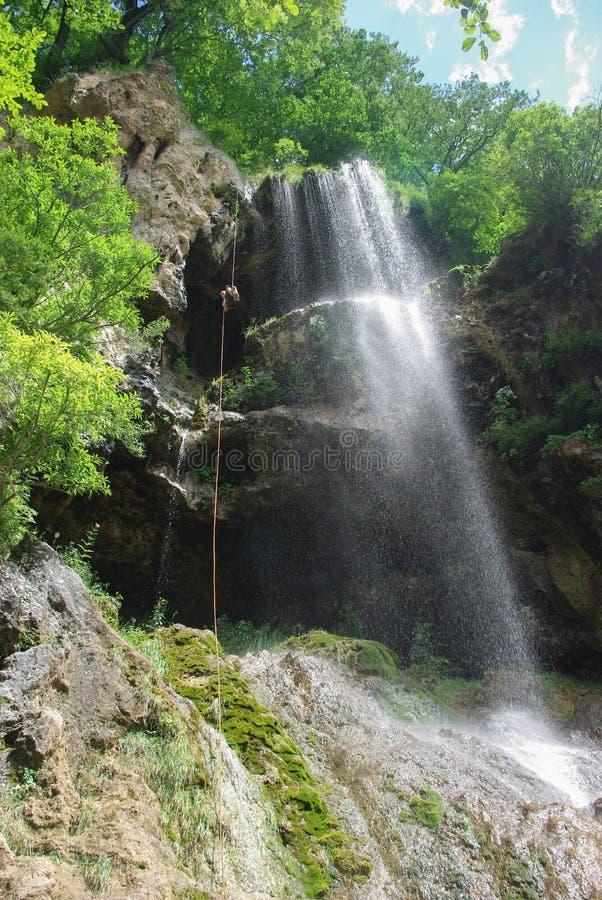 Ansicht von unten des Mannes Seil nahe Wasserfall oben kletternd, Russische Föderation, Kaukasus, lizenzfreie stockbilder