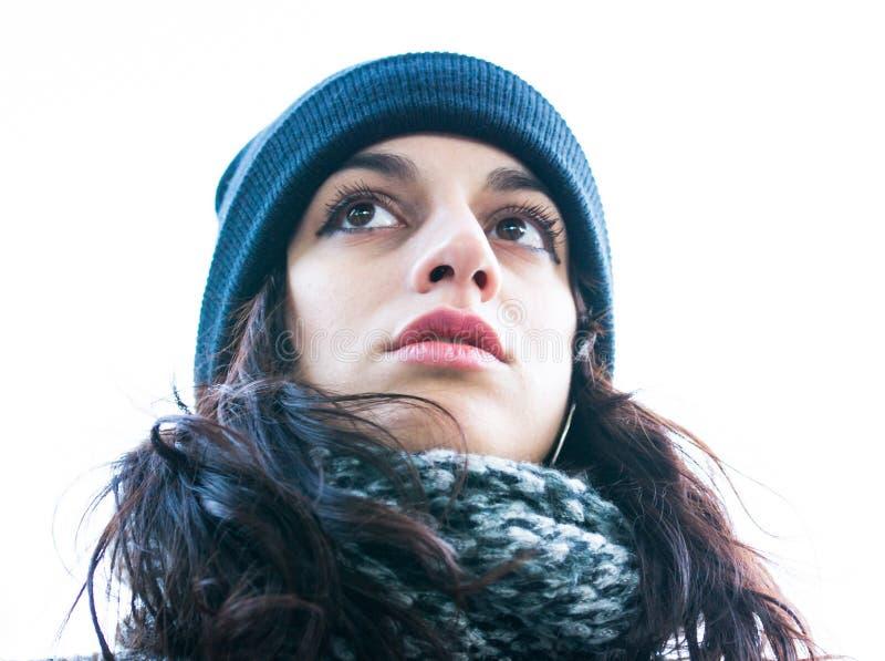 Ansicht von unten des Porträts eines netten/schönen Mädchens, das vorwärts mit einem Hut und einem Schal schaut lizenzfreies stockfoto
