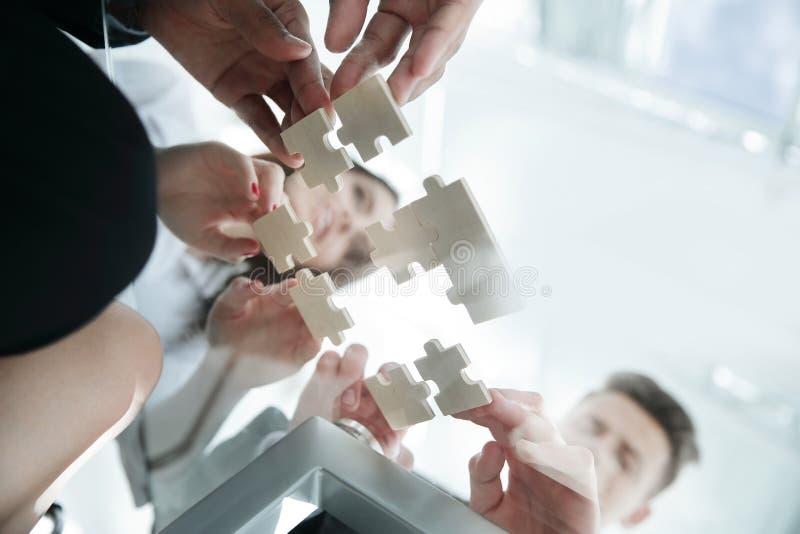 Ansicht von unten faltende Puzzlespielstücke des Geschäftsteams lizenzfreie stockfotos