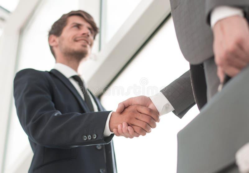 Ansicht von unten HändedruckTeilhaber im Büro lizenzfreie stockfotos