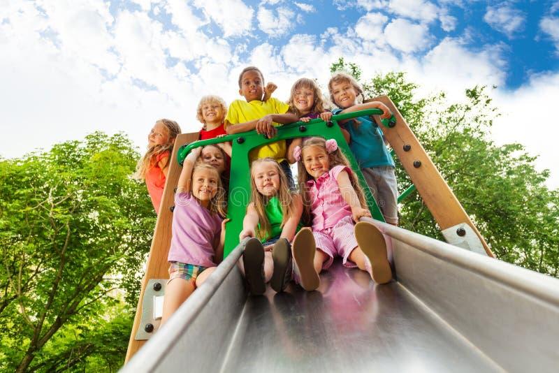 Ansicht von unterhalb vieler Kinder auf Spielplatzrutsche lizenzfreie stockfotografie