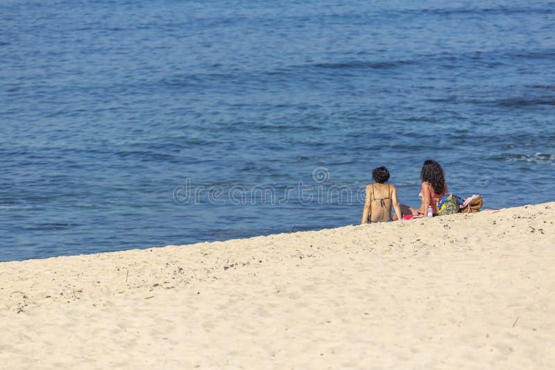 Ansicht von zwei Frauen, allein auf dem Strand, das Ein Sonnenbad nehmen auf dem Strand von Leca DA genießend lizenzfreies stockfoto