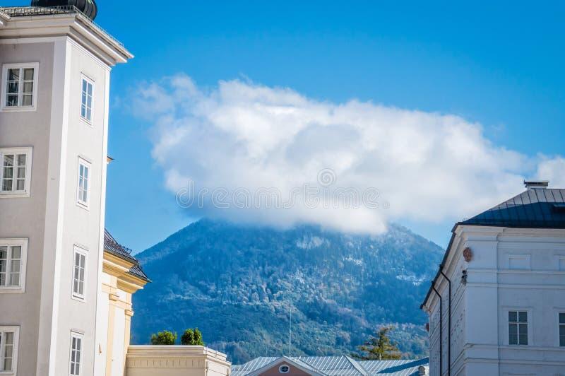 Ansicht zum Berg unter Wolke zwischen zwei Gebäuden in Salzburg Österreich stockfotos