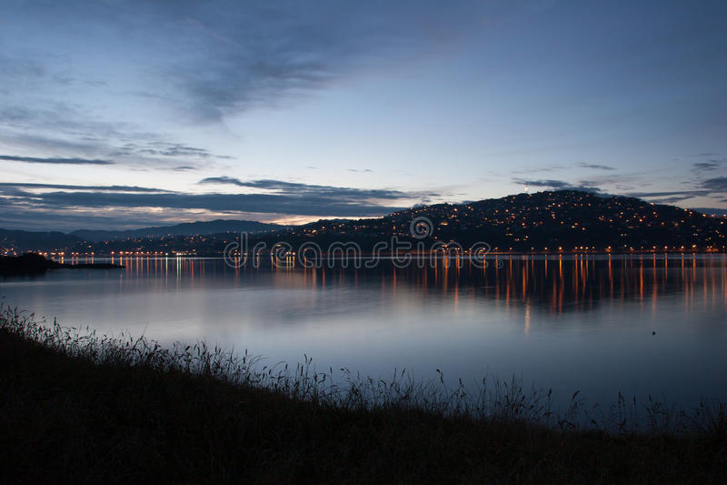 Ansicht zur Nachtstadt auf dem Hügel mit Lichtern von der Küste lizenzfreie stockbilder