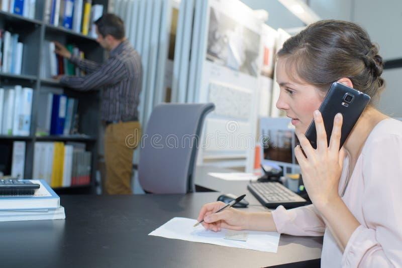 Ansichtfrau mit Telefon im Büro lizenzfreie stockfotografie