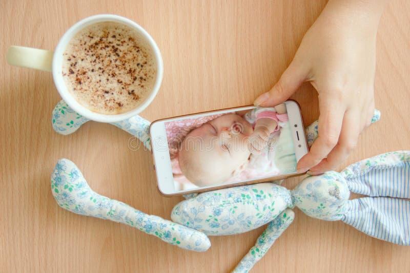 Ansichthandfarbvideo-Babymonitor Weibliche Hände halten einen Smartphone mit einer Babymonitor-APP Nahe heißem Getränk und Kinder lizenzfreies stockfoto