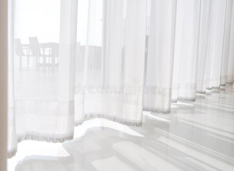 Ansichtmeerblick, der Gewebevorhänge des lichtdurchlässigen Weiß des Durchlaufs schaut und stockfoto