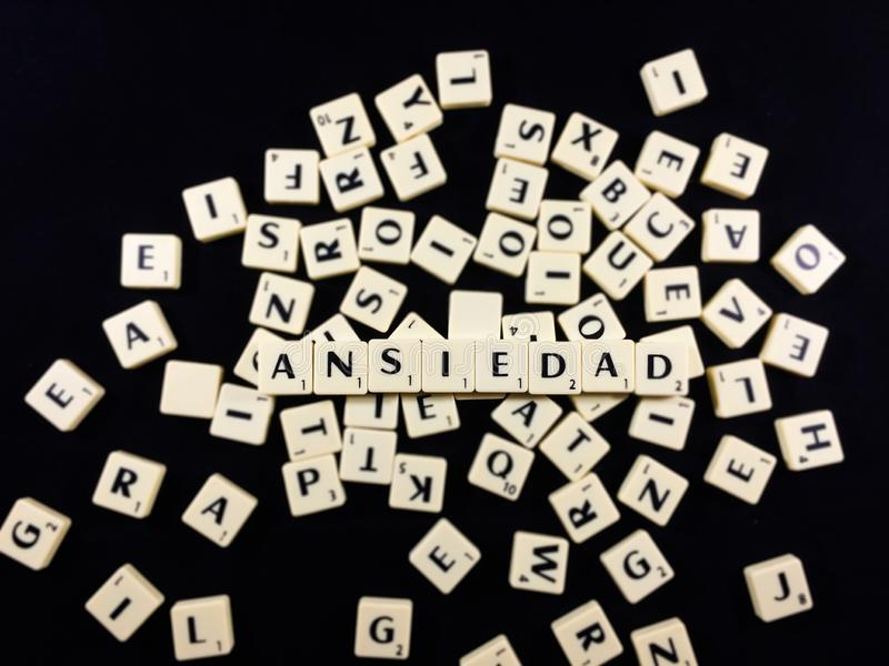 Ansiedad word spelled with letter tiles in black background stock photo
