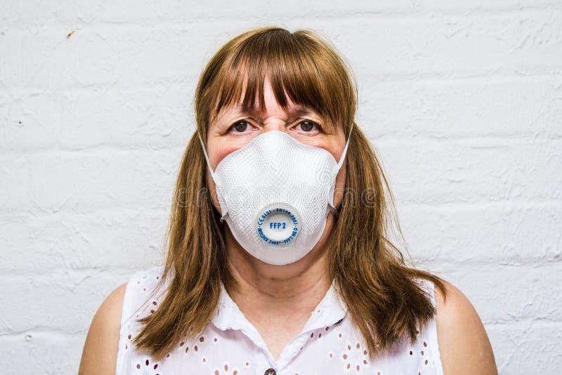 Ansikte på en kvinna som bar mask för kirurgiska ingrepp under Covid 19 arkivbilder