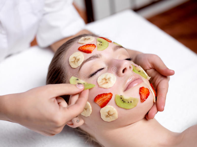 ansikts- fruktmaskering som mottar salongbrunnsortkvinnan arkivbild