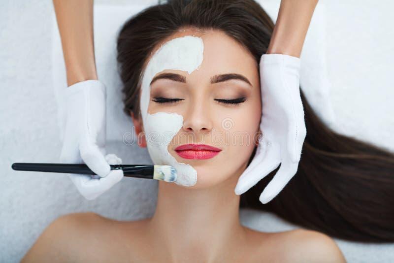 Ansikts- hudomsorg Härlig kvinna som får den kosmetiska maskeringen i salong royaltyfri bild