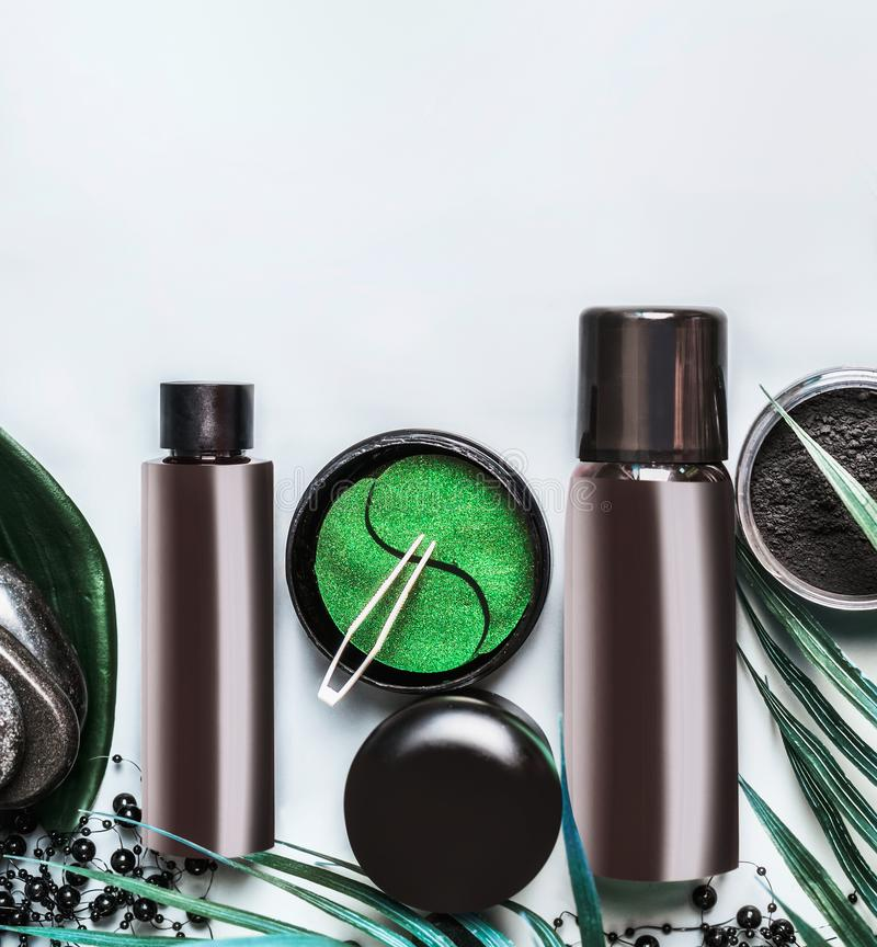 Ansikts- kosmetisk produktuppsättning i svart och brunt förpacka Modern hudomsorg med ögonlappen och kolpulver på ljus bakgrund royaltyfri bild