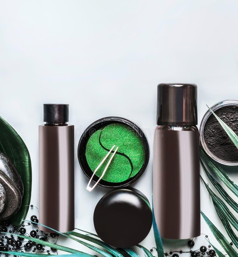 Ansikts- kosmetisk produktuppsättning i svart och brunt förpacka Modern hudomsorg med ögonlappen och kolpulver på ljus bakgrund arkivfoto