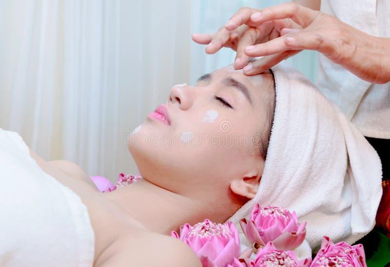 Ansikts- maskering för asiatisk kvinnahälerilera i brunnsortskönhetsalong arkivbilder