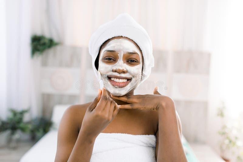 Ansikts- maskering för vitamin Afrikansk le kvinna med en framsida i en maskering i brunnsort arkivfoton