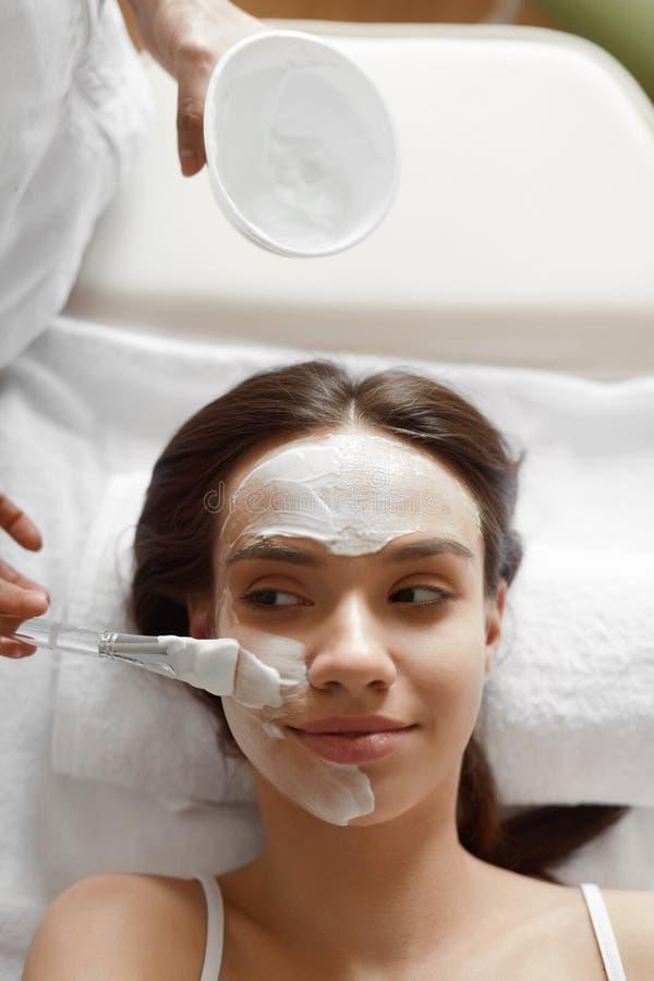 Ansikts- skönhetbehandling Härlig kvinna som får den kosmetiska maskeringen arkivbild