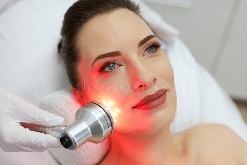 Ansikts- skönhetbehandling Kvinna som gör röd ledd ljus terapi arkivbild