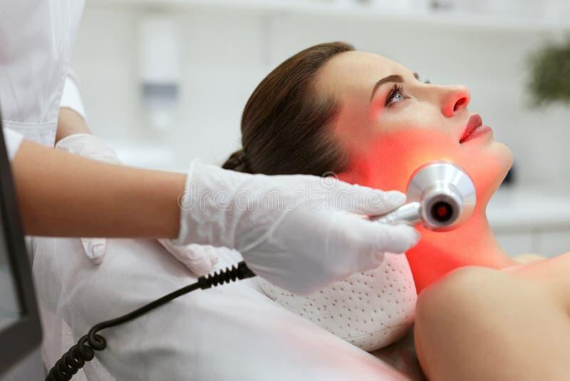 Ansikts- skönhetbehandling Kvinna som gör röd ledd ljus terapi arkivfoto