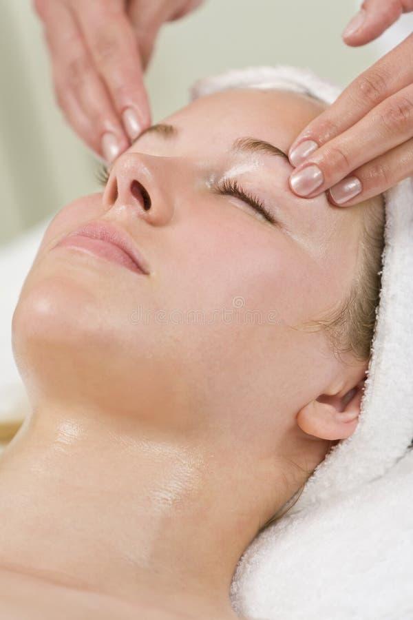 ansiktsbehandlingen får den head massagen den avslappnande brunnsortkvinnan royaltyfri fotografi