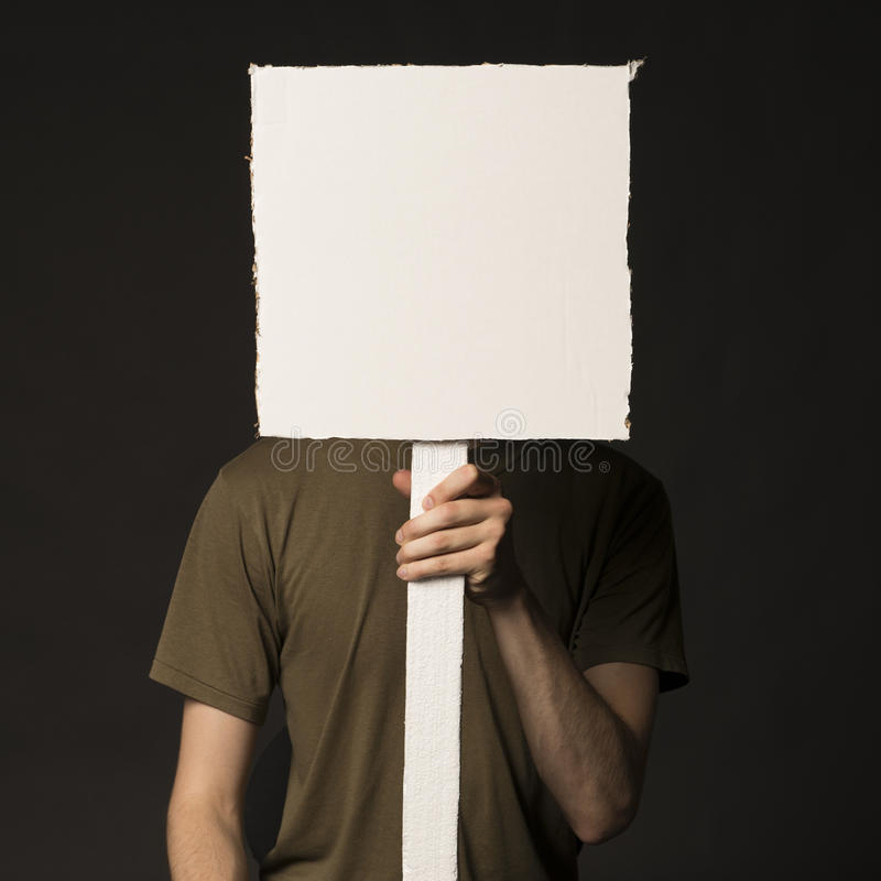 Ansiktslös person som rymmer ett tomt tecken arkivfoto