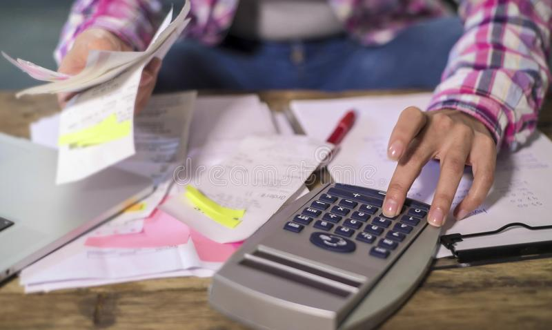 Ansiktslösa anonyma kvinnahänder som arbetar med bankskrivbordsarbeteräkningar och finansiella dokument som beräknar månadstidnin royaltyfria foton