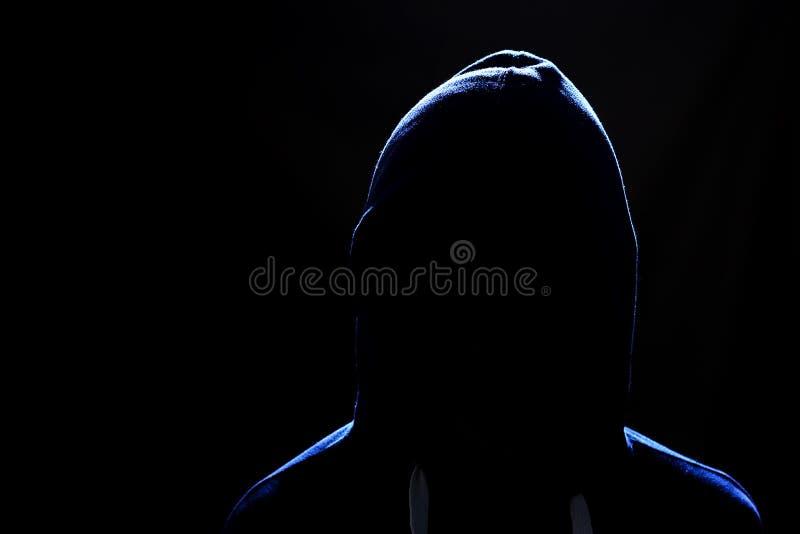 Ansiktslöst mänskligt diagram i en huv på en svart bakgrund arkivfoton