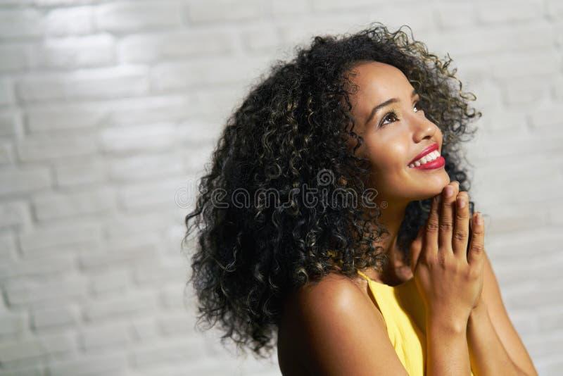 Ansiktsuttryck av den unga svarta kvinnan på tegelstenväggen royaltyfri bild