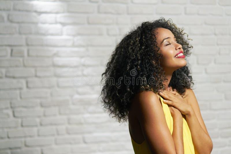 Ansiktsuttryck av den unga svarta kvinnan på tegelstenväggen arkivbilder