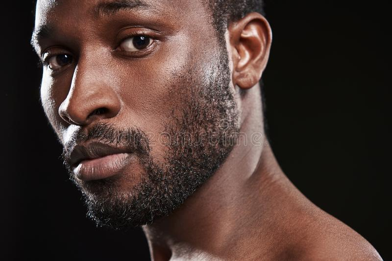 Ansiktsuttryck av en le afro amerikansk man mot svart bakgrund arkivfoto