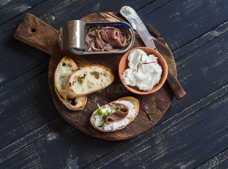 Ansjovis en geitkaassandwich op rustieke houten raad stock afbeeldingen